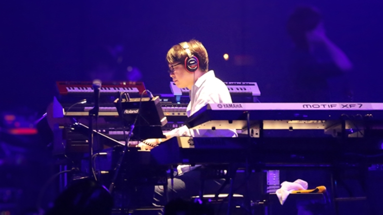 Akimitsu Honma on stage, surrounded by keyboards
