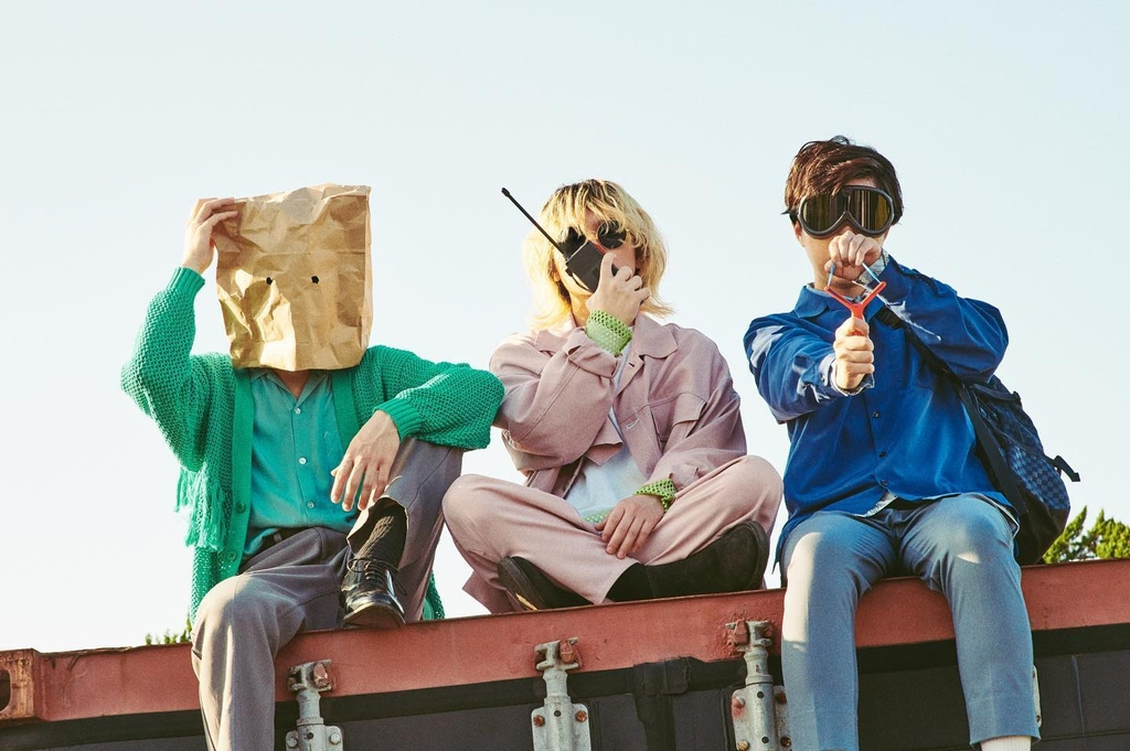 3 members, outdoors, sky is background, person on left wears paper pag on head