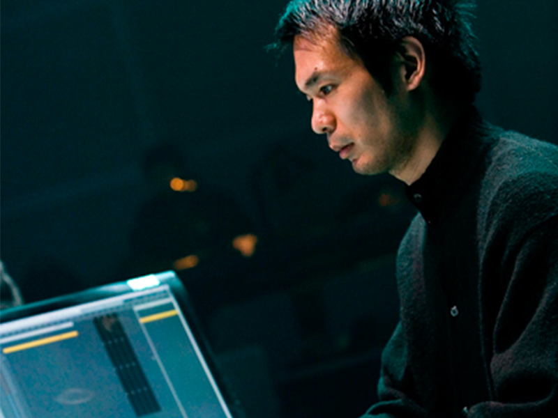 man, sits, computer screen, black cardigan, blurred background, in a dark room