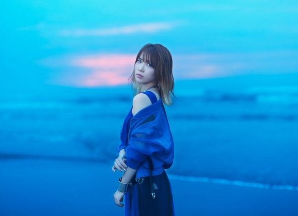 May'n, outdoors, wears blue blouse, sky is background