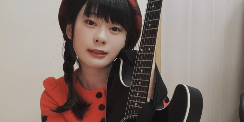 pigtails, red-black plaid beret, red blouse, holds black guitar close to face