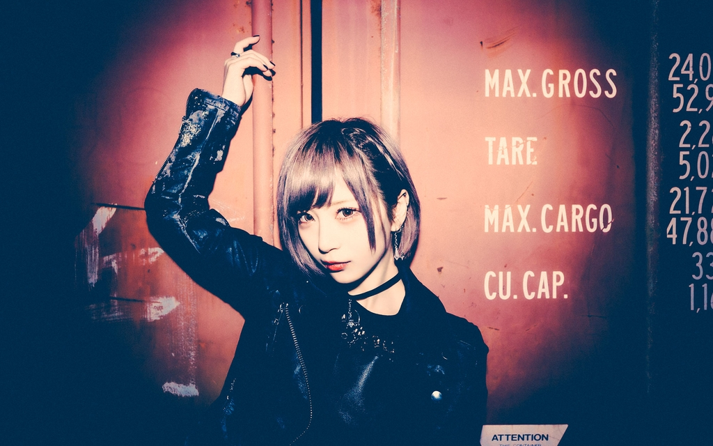 female, container, black top, black long sleeve jacket, holds right hand up high