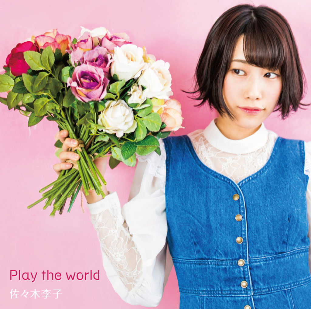 holds bouquet of roses, pink background, white top, blue denim vest
