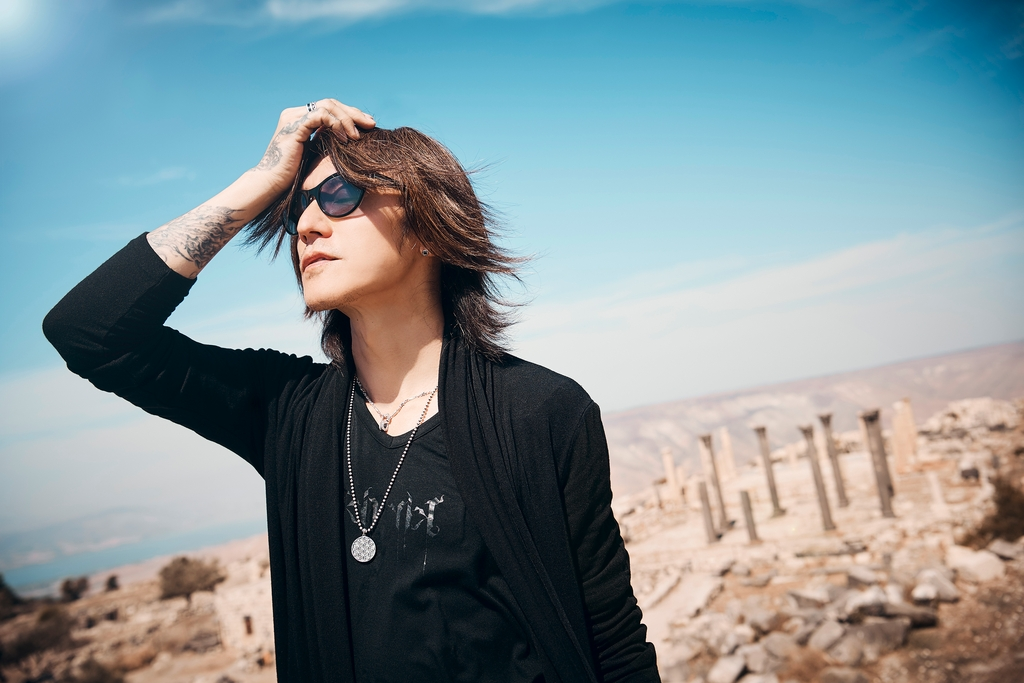 man, holds head, wears black clothing, sunglasses, outdoors, blue sky, ancient ruins