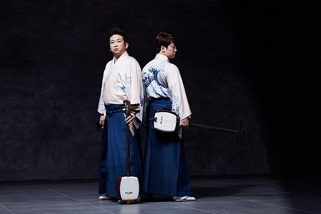 two men, standing back to back, traditional Japanese clothing, shamisen