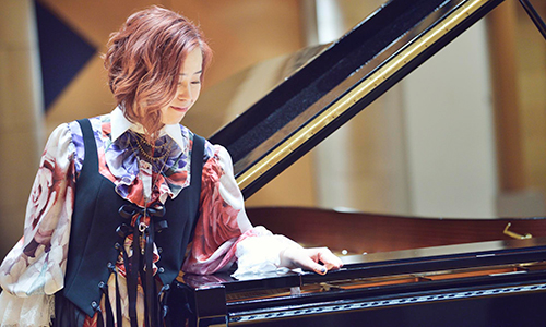woman, smiles, standing, black grand piano, slightly leans on it