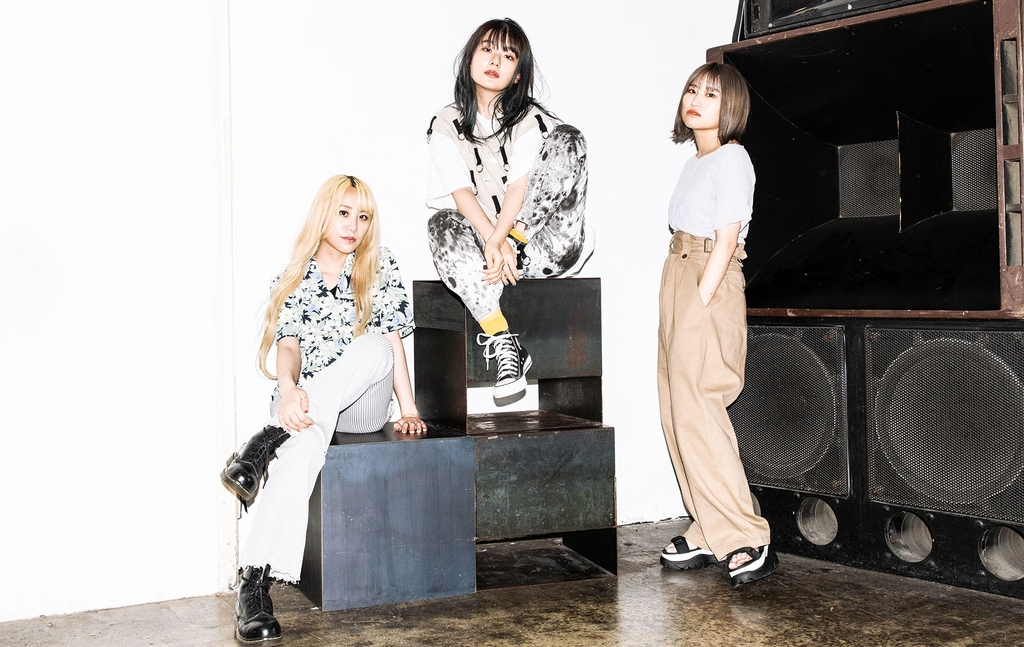 3 young women, near music equipment, casual clothing, looking at the camera