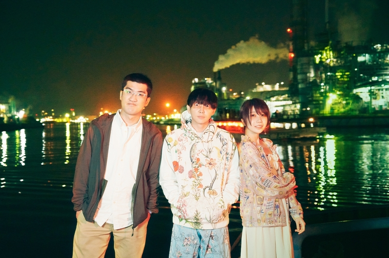 three Shinsei Kamattechan members, night, waterfront behind them.